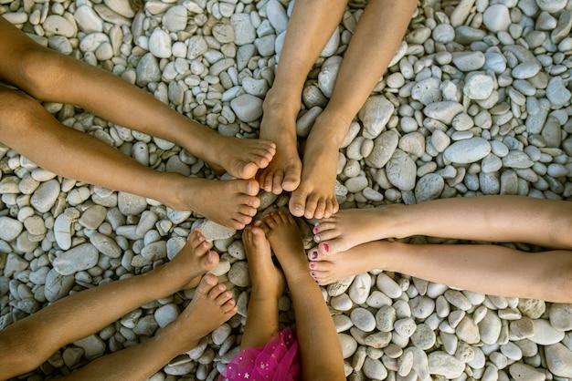 Vista superior dos pés de cinco crianças em forma de estrela em praia de seixos