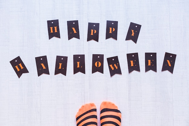 Vista superior dos pés de uma mulher com letras de um feliz dia das bruxas no chão. mulher vestindo uma malha preta e laranja listras. conceito. interior e estilo de vida