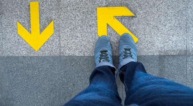 Vista superior dos pés do homem que estão sobre o símbolo da seta na plataforma do metro.