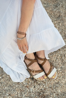 Vista superior dos pés femininos em sandálias na praia de areia.