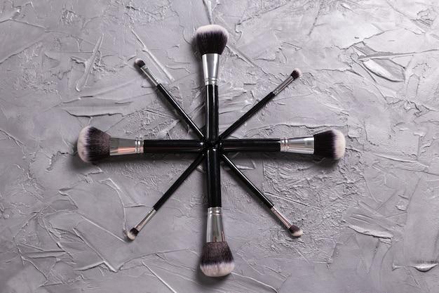 Vista superior dos pincéis de maquiagem em fundo cinza