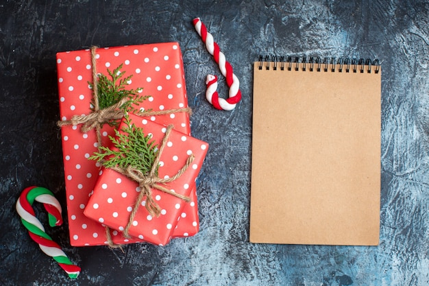 Vista superior dos presentes de natal, bengala e caderno vazio