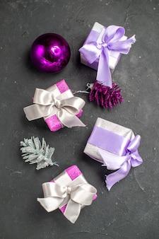 Vista superior dos presentes de natal rosa e roxo com fitas, brinquedos da árvore de natal na superfície isolada escura.