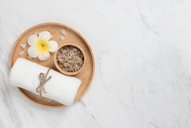 Vista superior dos produtos de spa na bandeja de madeira em forma redonda em mármore branco.