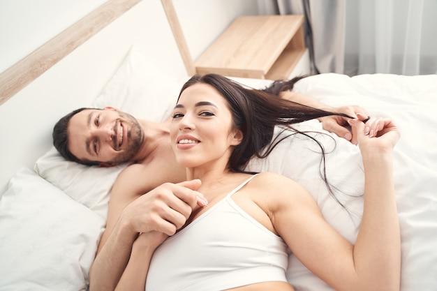 Vista superior dos recém-casados satisfeitos posando na cama para a frente