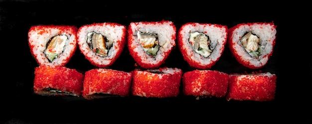 Vista superior dos rolos japoneses triangulares vermelhos em um fundo preto.