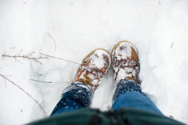 Vista superior dos sapatos na neve fresca. inverno. primeira vista de botas marrons