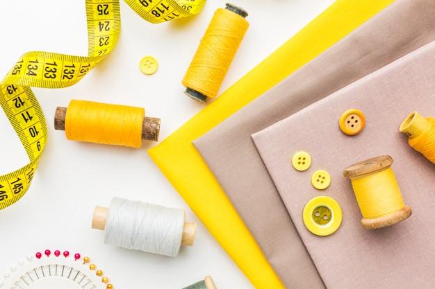Vista superior dos tecidos com botões e fita métrica