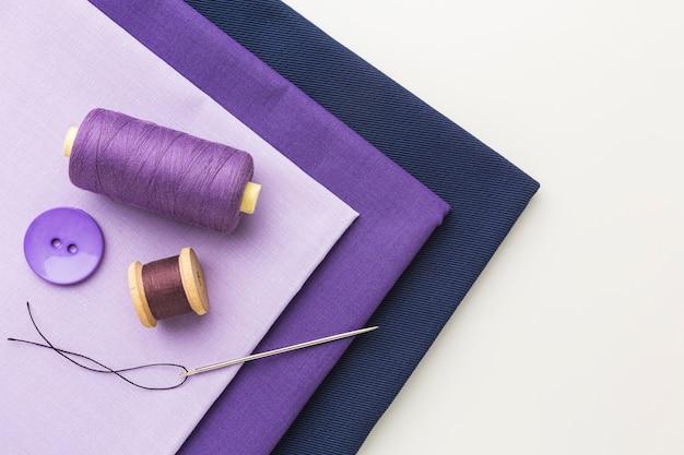 Vista superior dos tecidos com linha e botão