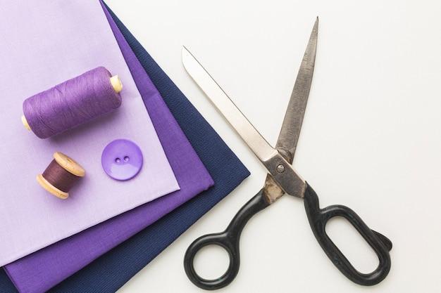 Vista superior dos tecidos com tesoura e botão