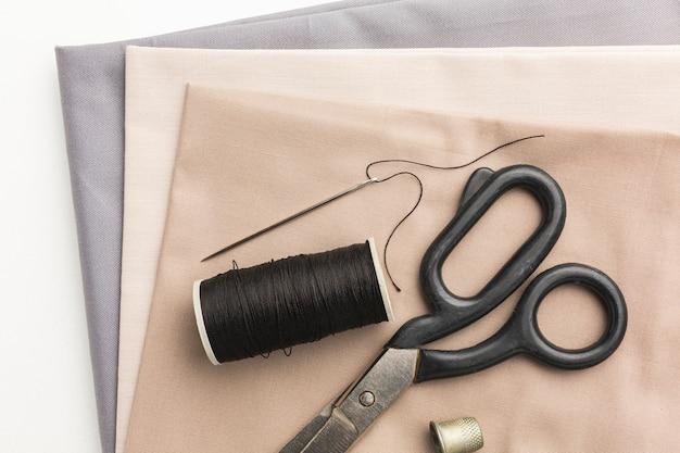 Vista superior dos tecidos com tesoura e dedal