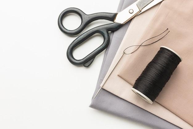 Vista superior dos tecidos com tesoura e linha