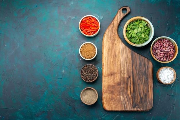 Vista superior dos temperos e verduras com feijão no fundo azul escuro, foto colorida do tempero do produto