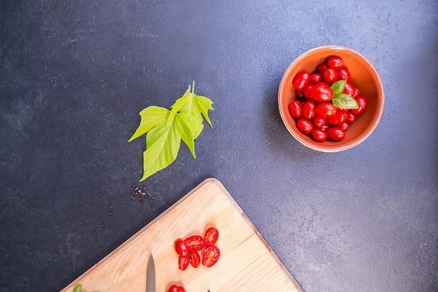 Vista superior dos tomates-cereja frescos na placa de madeira em uma mesa