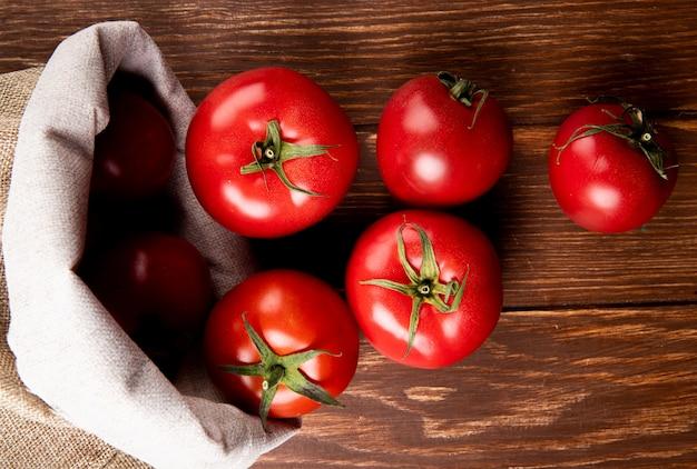 Vista superior dos tomates derramando fora do saco na superfície de madeira