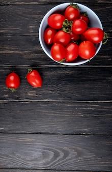 Vista superior dos tomates em uma tigela de madeira com espaço de cópia