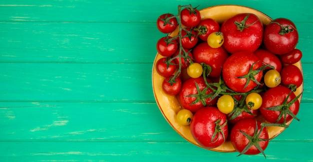 Vista superior dos tomates em uma tigela no lado direito e na superfície verde com espaço de cópia