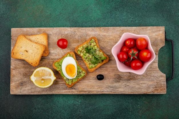 Vista superior dos tomates em uma tigela rosa em uma placa de madeira da cozinha com fatias de pão torradas com polpa de abacate e ovo na superfície verde