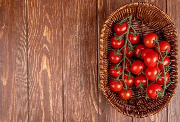 Vista superior dos tomates na cesta no lado direito e superfície de madeira com espaço de cópia