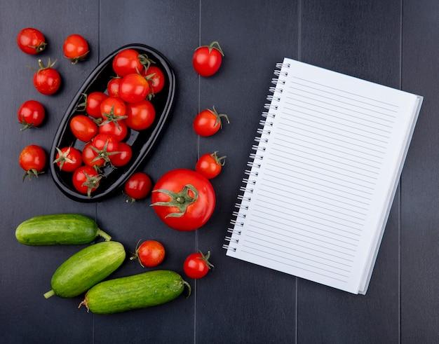 Vista superior dos tomates no prato com pepinos e bloco de notas na superfície preta