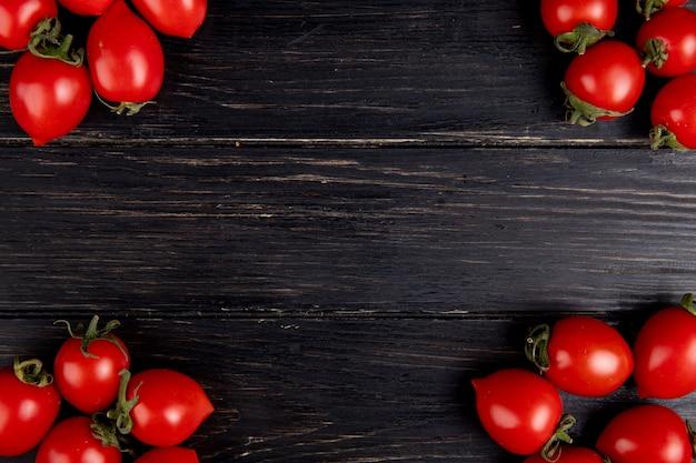 Vista superior dos tomates nos lados esquerdo e direito e superfície de madeira com espaço de cópia