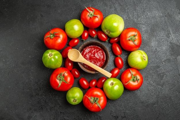 Vista superior dos tomates vermelhos e verdes cereja em torno de uma tigela com ketchup e uma colher de pau em um solo escuro com espaço de cópia