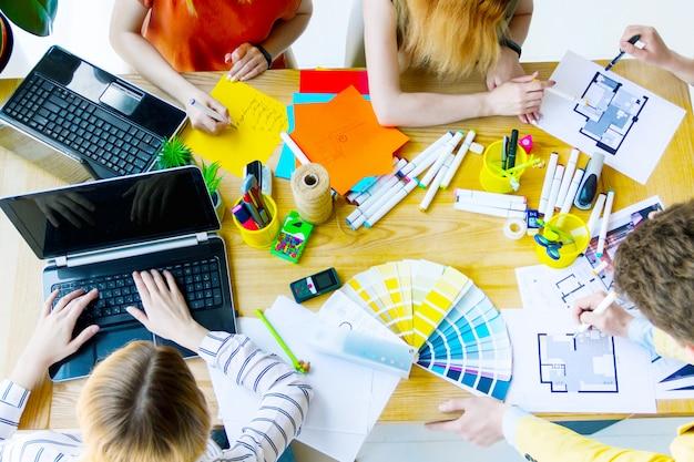 Vista superior dos trabalhadores criativos tendo reunião no gabinete. arquitetos e designers de interiores discutindo projeto de design com amostras de cores, layouts de sala, laptops, enquanto está sentado na mesa. conceito de trabalho em equipe.