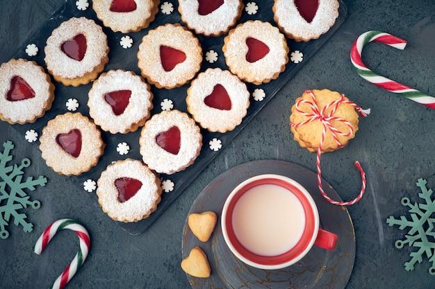 Vista superior dos tradicionais biscoitos de natal linzer com geléia vermelha no escuro, decorada com flocos de neve e bastões de doces