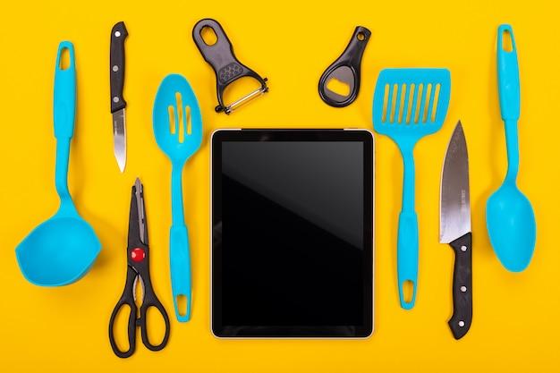 Vista superior dos utensílios de tablet e cozinha ao lado isolado em amarelo