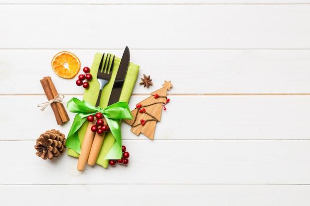 Vista superior dos utensílios no guardanapo festivo em madeira, decorações de natal com frutas secas e canela, conceito de jantar de ano novo