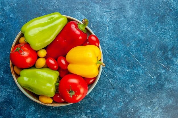 Vista superior dos vegetais de cores diferentes, pimentão, tomate, cereja, tomate, cereja, tigela, mesa, azul