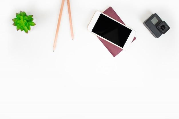 Vista superior dos viajantes com viagens de smartphone, câmera, passaporte e viagens em fundo branco.