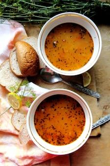 Vista superior duas sopas de lentilha com endro de limão e fatias de pão