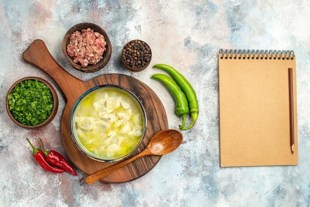 Vista superior dushbara uma colher de pau em tigelas de tábua de cortar com verduras de carne, pimenta preta, pimenta preta, um lápis, caderno, superfície nua