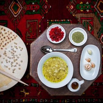 Vista superior dushpara com sementes de romã e vinagre e massa de pão na mesa