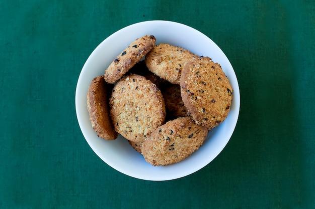 Vista superior e aérea de biscoitos de chocolate em uma tigela no guardanapo com fundo de madeira rústico.