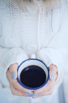Vista superior e close-up mãos de mulher segurando uma xícara quente de café ou chá no frio