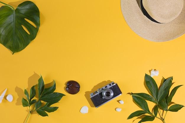 Vista superior e plana leigos de fundo amarelo para férias de verão, câmera fotográfica, chapéu, folha de palmeira. copie o espaço.