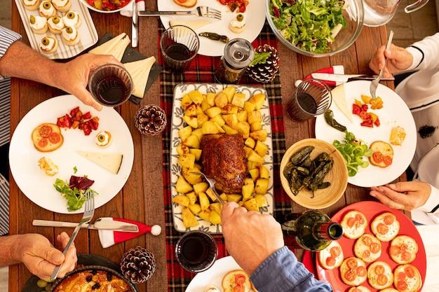Vista superior e superior em uma grande mesa de madeira cheia de comida como frango e um grupo de pessoas comendo e pegando comida do meio da mesa