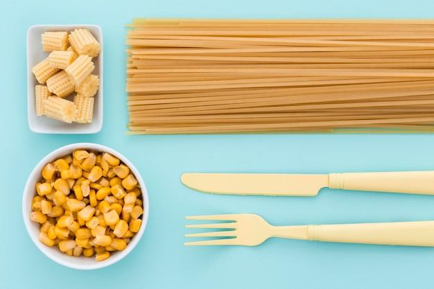 Vista superior elegante talheres com macarrão e milho