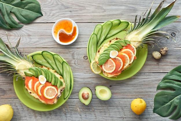 Vista superior em barcos de abacaxi com salmão defumado e fatias de abacate com ovos de limão e codorna, plana leigos na mesa de madeira velha