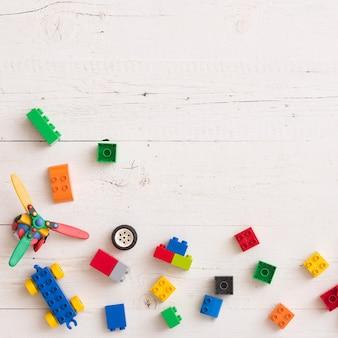Vista superior em brinquedos, cubos de madeira com números e tijolos de plástico em fundo branco de madeira