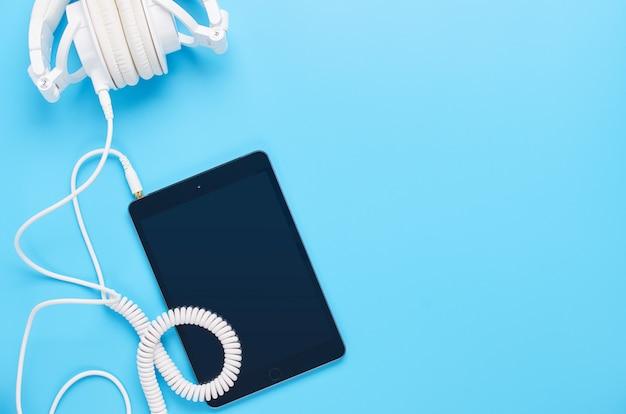 Vista superior em cima de gadgets sobre fundo azul, composição de fones de ouvido brancos e tablet