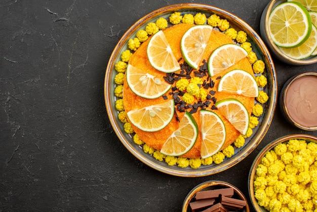 Vista superior em close-up apetitoso bolo de bolo com chocolate e frutas cítricas taças de lima de chocolate, rebuçados amarelos e creme de chocolate na mesa preta