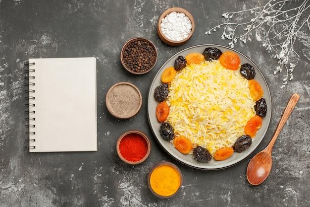 Vista superior em close-up arroz arroz com frutas secas no prato cinco tigelas de caderno branco de especiarias