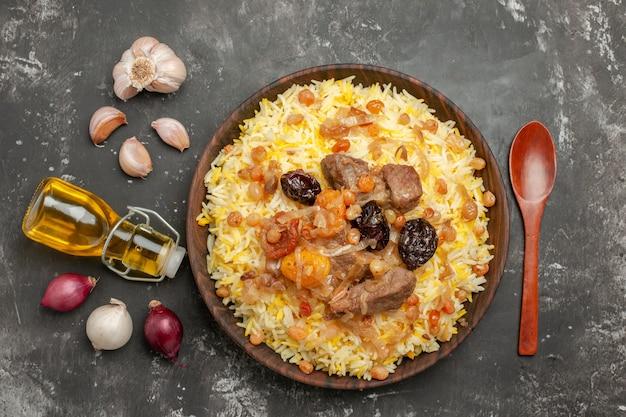 Vista superior em close-up arroz cebola alho garrafa de colher de óleo um pilaf apetitoso