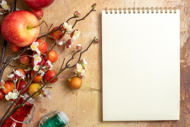 Vista superior em close-up bagas caderno branco cerejas ramos de árvores com garrafas de flores