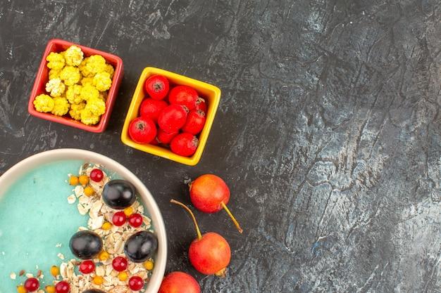 Vista superior em close-up bagas groselha uvas pretas aveia no prato doces amarelos cereja
