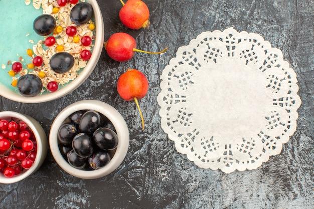 Vista superior em close-up bagas groselha uvas pretas aveia no prato rendas cereja guardanapo