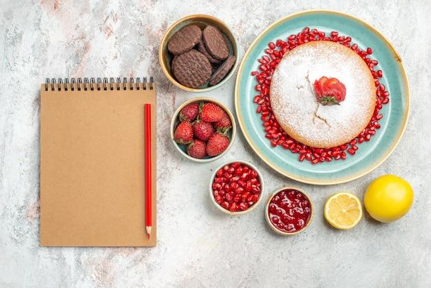 Vista superior em close-up biscoitos caderno lápis bolo frutas cítricas bolo de morangos e tigelas de romã com diferentes biscoitos de frutas vermelhas na mesa